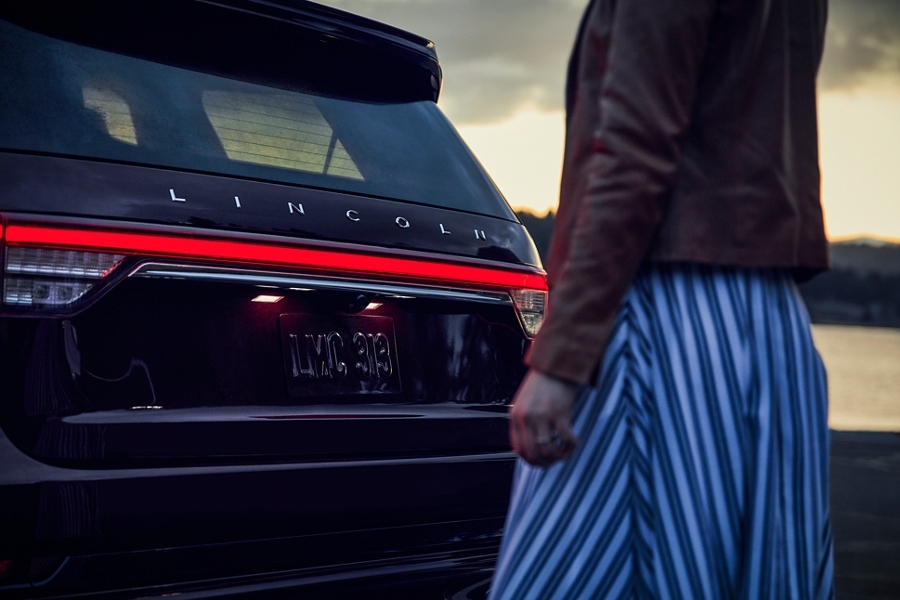 A woman is shown approaching the rear of a 2021 Lincoln Aviator which have the taillamps illuminated as part of the Lincoln Embrace experience