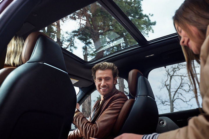 A family is shown in a parked 2021 Lincoln Aviator with the panoramic vista roof above them allowing golden light into the cabin