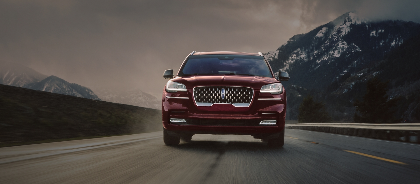 A 2021 Lincoln Aviator Grand Touring is shown being driven on a winding mountain road