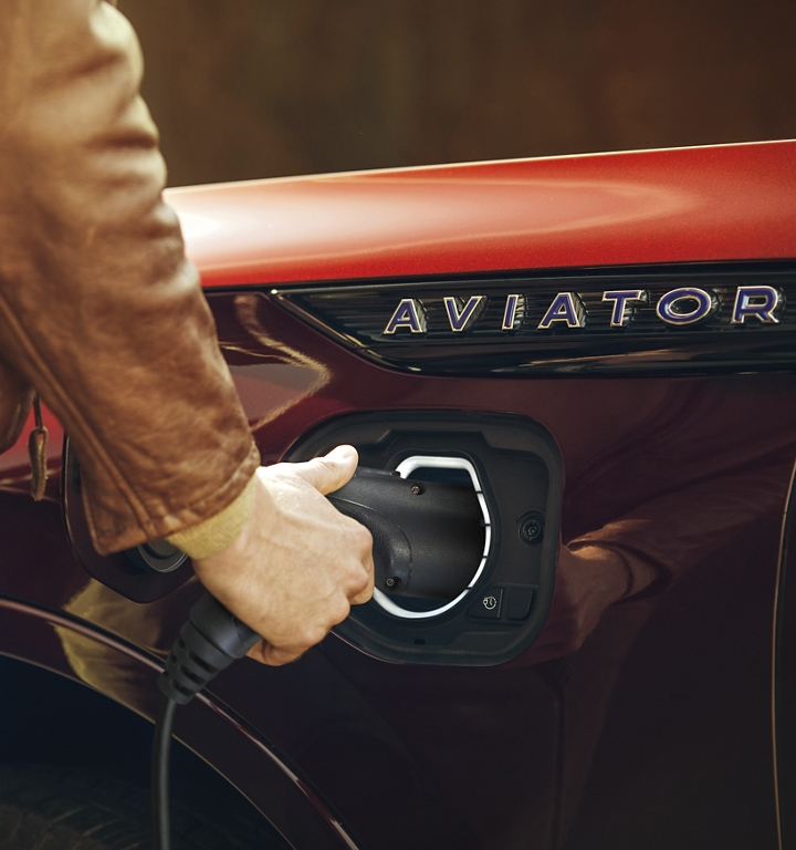 A person is shown disconnecting the at home charger from a 2021 Lincoln Aviator