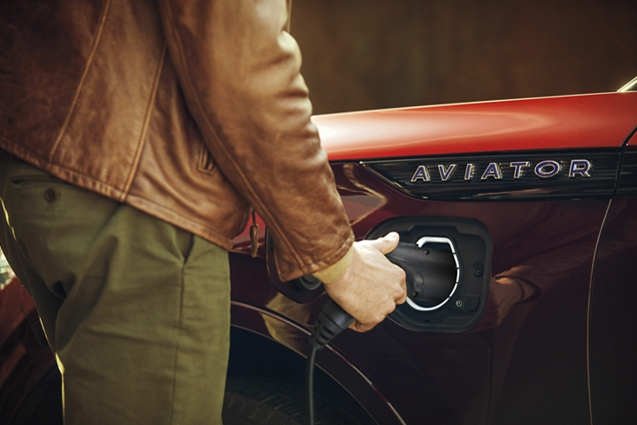 A hand is shown easily using the at home charging station that helps to power the 2021 Lincoln Aviator Grand Touring model