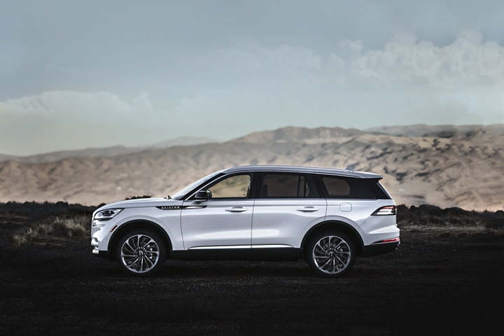 A 2021 Lincoln Aviator in the Pristine White exterior color is shown parked at a scenic mountain overlook