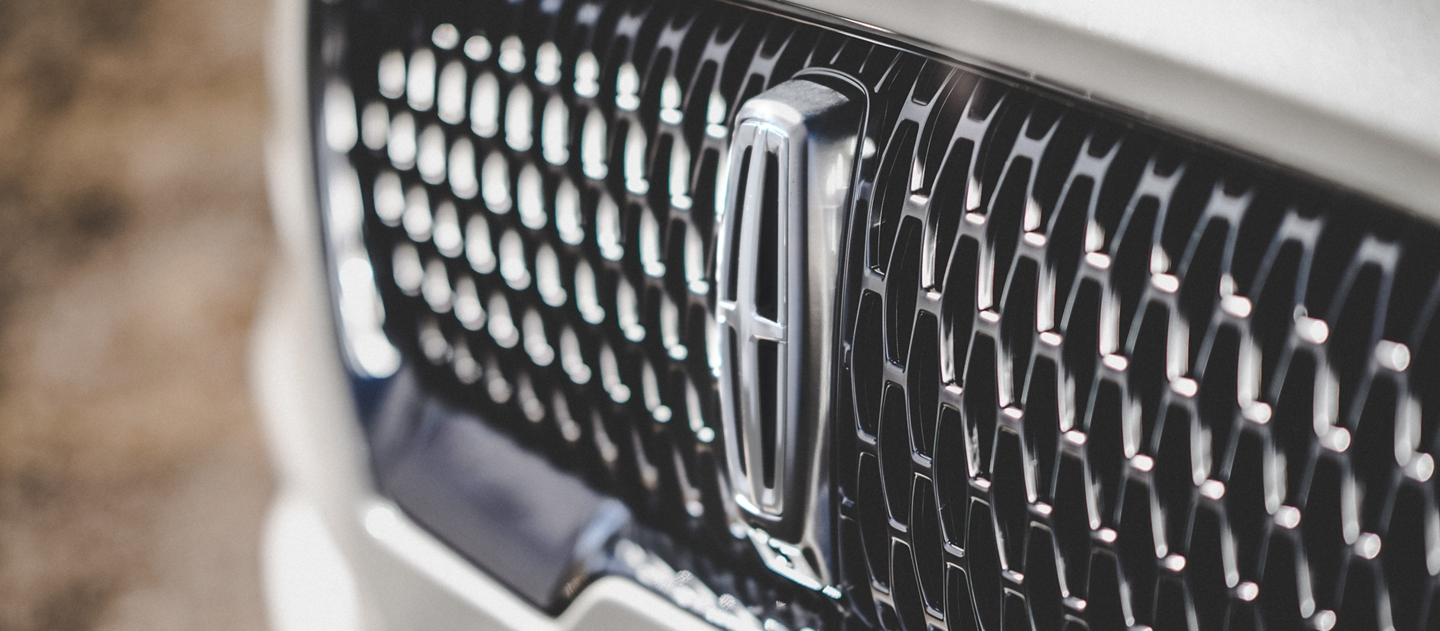 The grille of the 2021 Lincoln Aviator Reserve model is shown which uses an eye catching repeated field of Lincoln Star emblem shapes