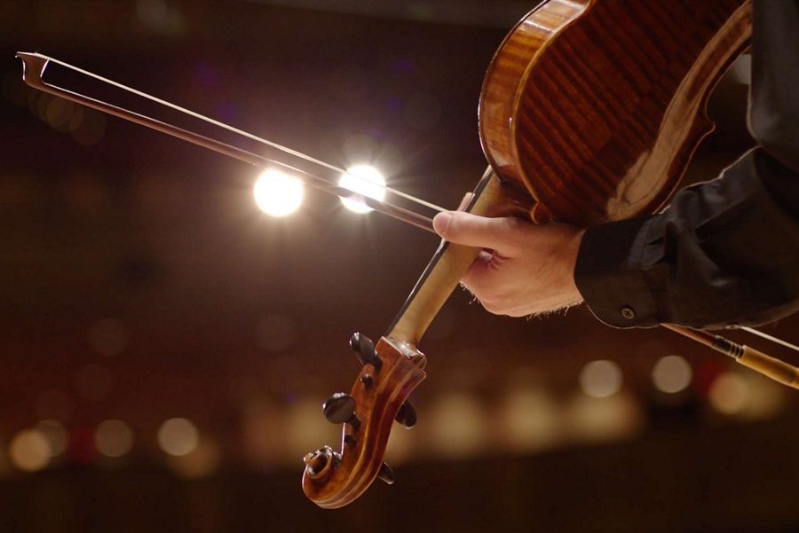 A hand is shown holding a violin to indicate the Detroit Symphony Orchestras recording of vehicle chimes