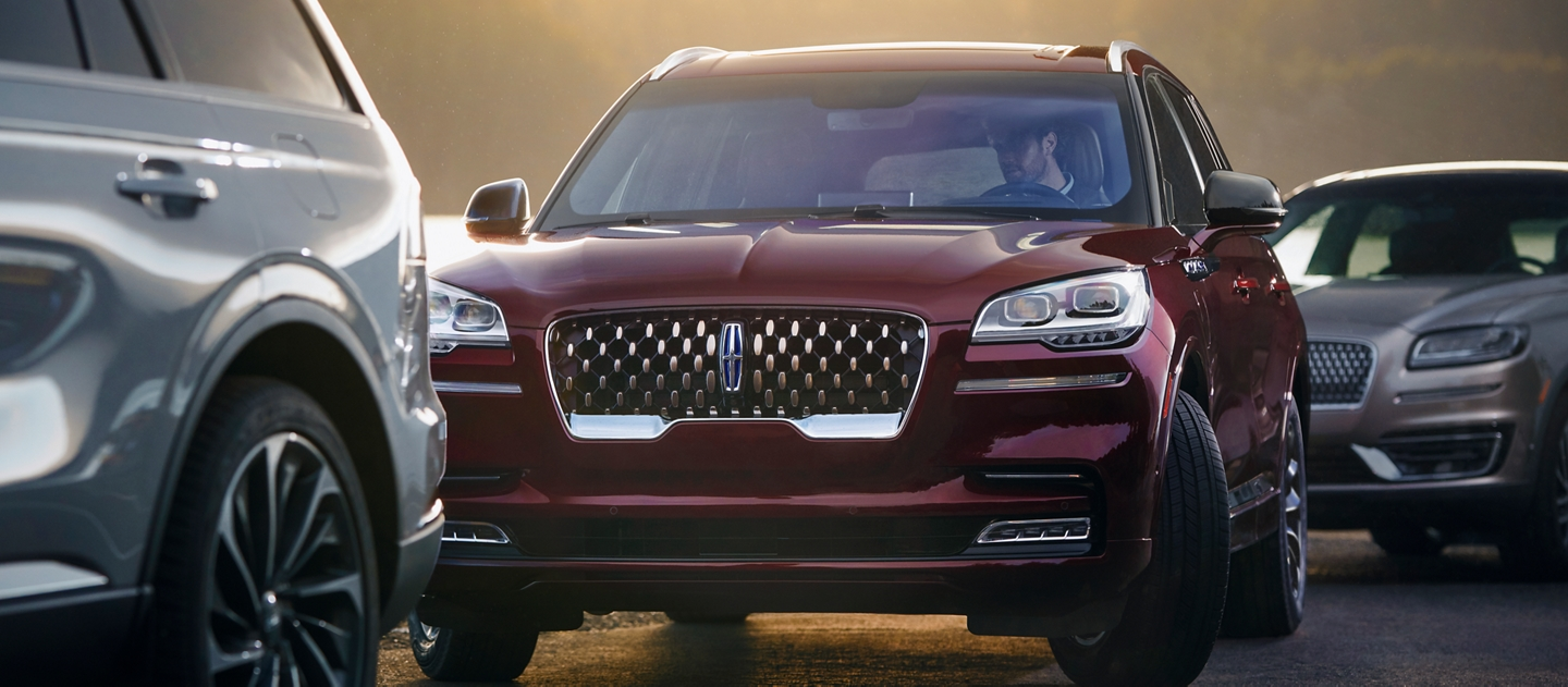 A 2021 Lincoln Aviator is shown using the active park assist plus system to park itself between two other vehicles
