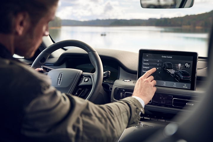 The driver in a parked 2021 Lincoln Aviator is shown adjusting the adaptive cruise control settings in the center touchscreen