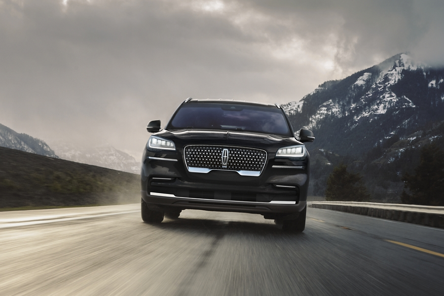 A 2021 Lincoln Aviator is shown being driven near a mountain
