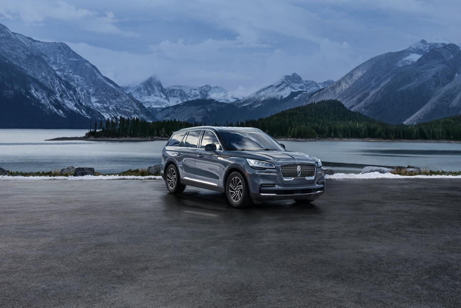 A 2021 Lincoln Aviator is shown parked by a lake with snow capped mountains in the background