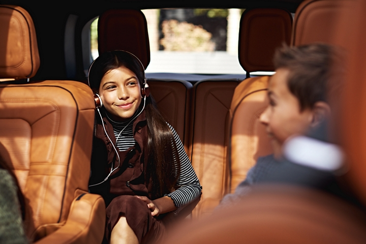 A young girl is shown seated comfortably in the third row of a 2021 Lincoln Aviator