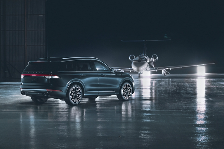 A 2021 Lincoln Aviator Black Label is shown parked on a runway with a private jet in the background