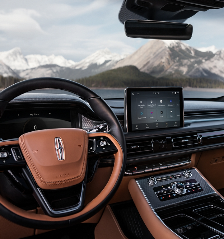 The steering wheel of a 2021 Lincoln Aviator is featured with snow capped mountains shown through the windshield