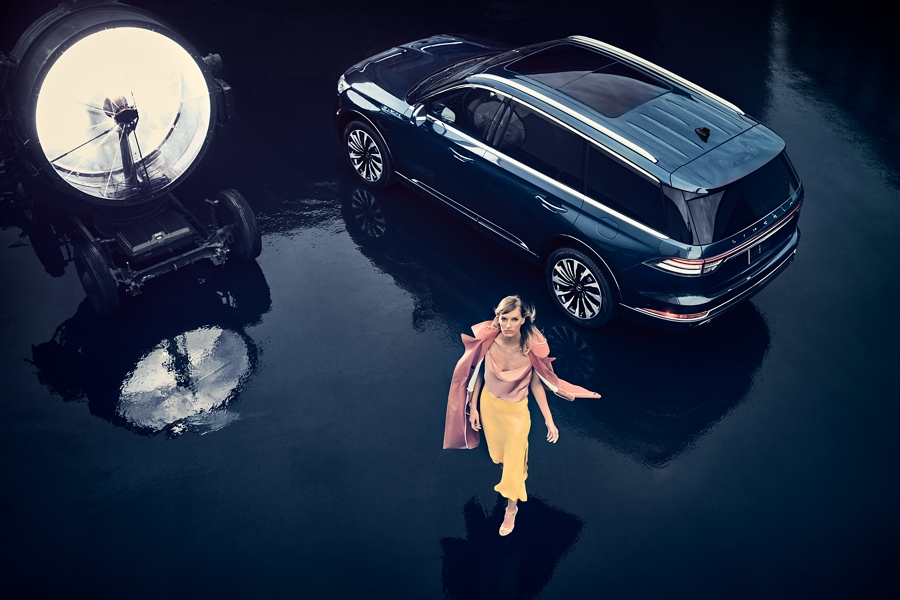 A woman is shown walking away from a 2021 Lincoln Aviator Black Label Grand Touring that is parked on the tarmac of a private airport