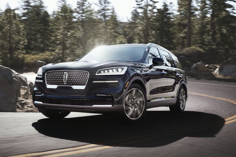 A 2021 Lincoln Aviator Black Label is shown being driven through a tight and steep mountainous curve