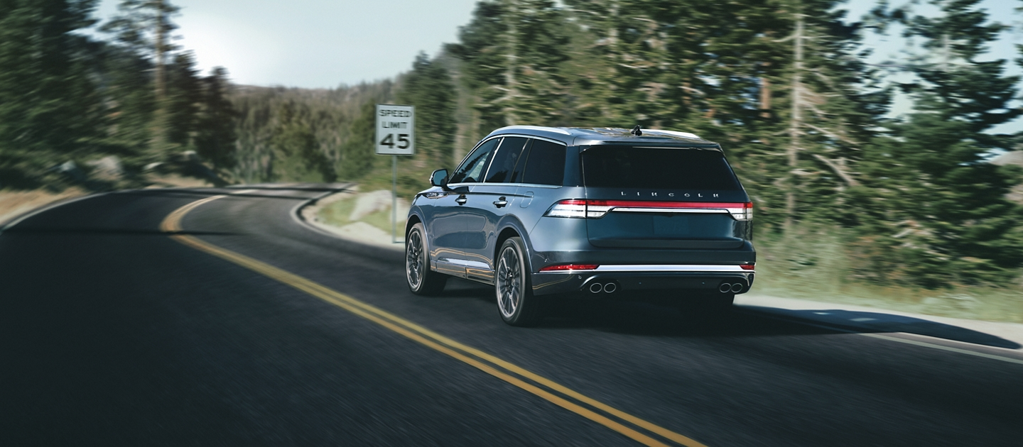 A 2021 Lincoln Aviator is shown being driven on a winding road as it approaches a speed limit sign