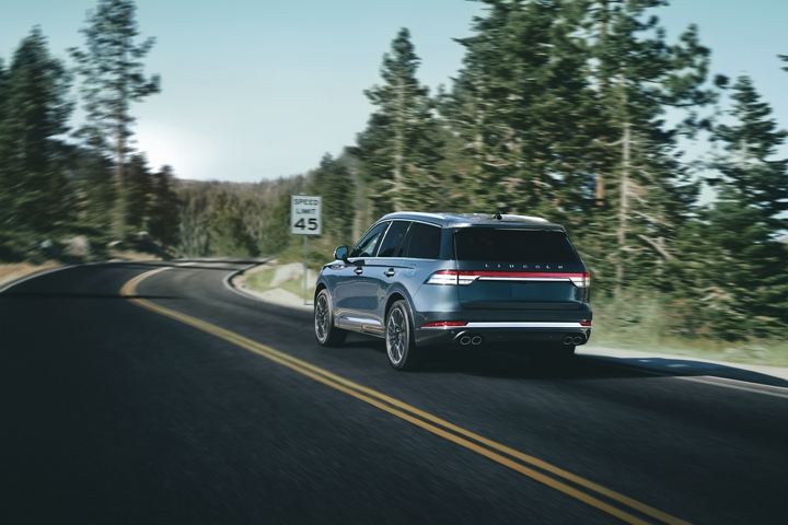 A 2021 Lincoln Aviator is shown being driven on a mountain road as it approaches a speed limit sign
