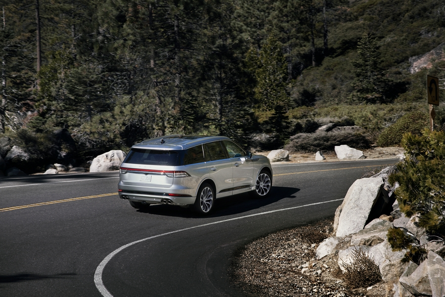A 2021 Lincoln Aviator is shown being driven through a sharp turn on a mountain road