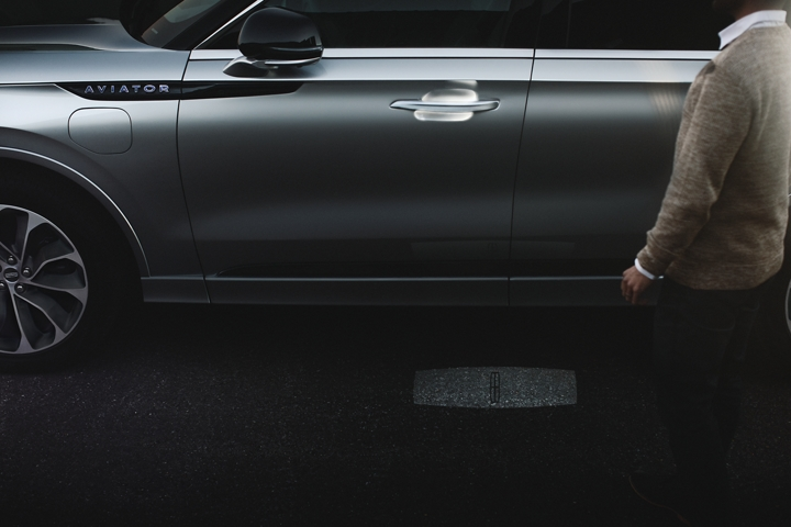 A person approaches a 2021 Lincoln Aviator Grand Touring as the Lincoln Embrace sequence of welcome lighting illuminates