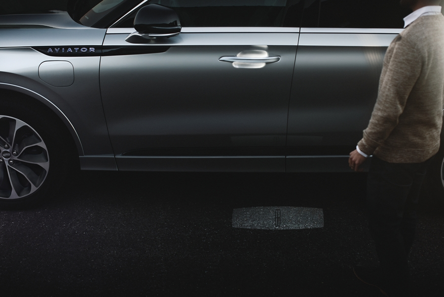 A person is shown approaching a 2021 Lincoln Aviator as an illuminated welcome mat is projected on the ground