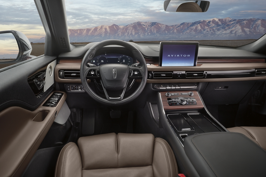 The front cabin of a 2021 Lincoln Aviator is shown with a remote mountain range shown through the windshield