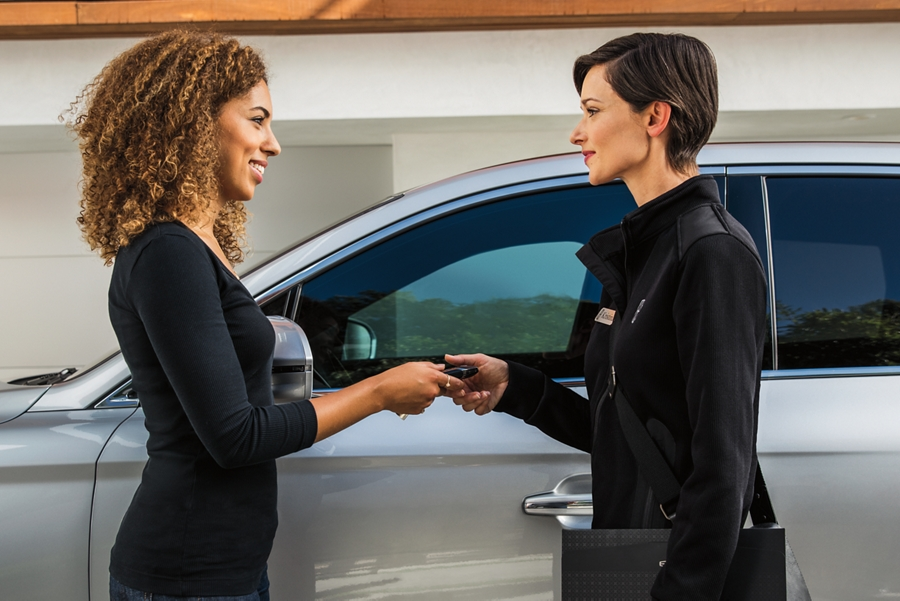 A woman is handing her key to a female Lincoln representative in front of a Lincoln vehicle for Pickup and Delivery