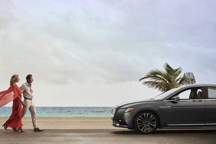 A couple is shown approaching a 2020 Lincoln Continental parked by an inviting sandy beach