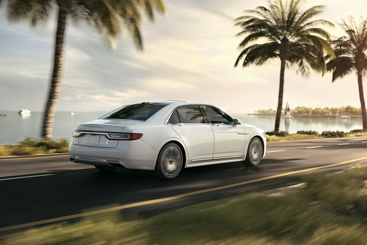 The 2020 Lincoln Continental shown in the Pristine White exterior color is being driven toward a warm sunset