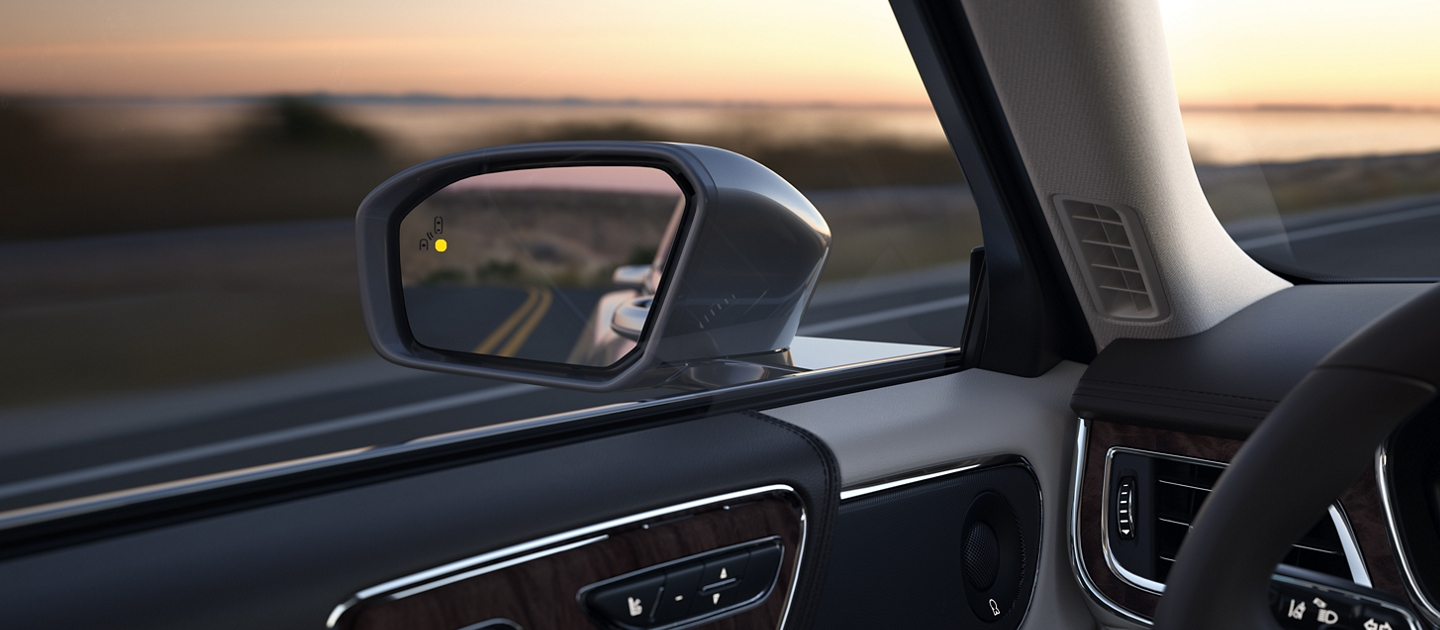 The drivers sideview mirror is shown with an illuminated indicator suggesting that a car is in the blind spot of the 2020 Lincoln Continental