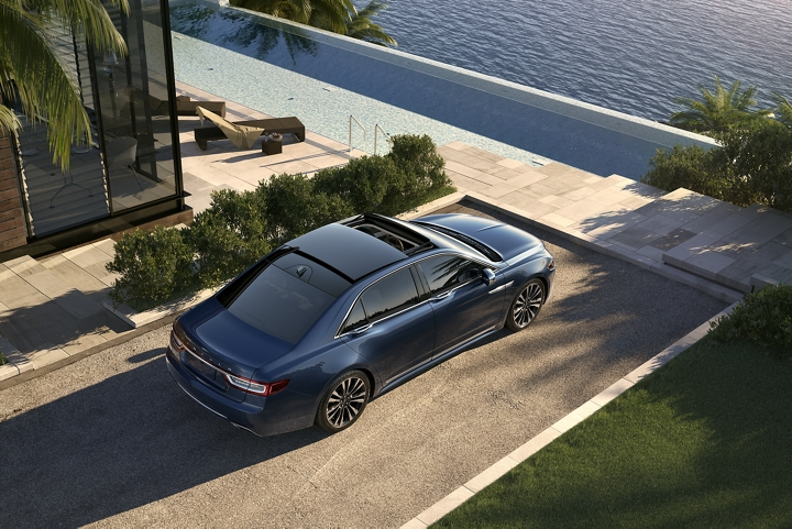 A 2020 Lincoln Continental in the Blue Diamond exterior color is parked in the driveway of an elegant shoreline home