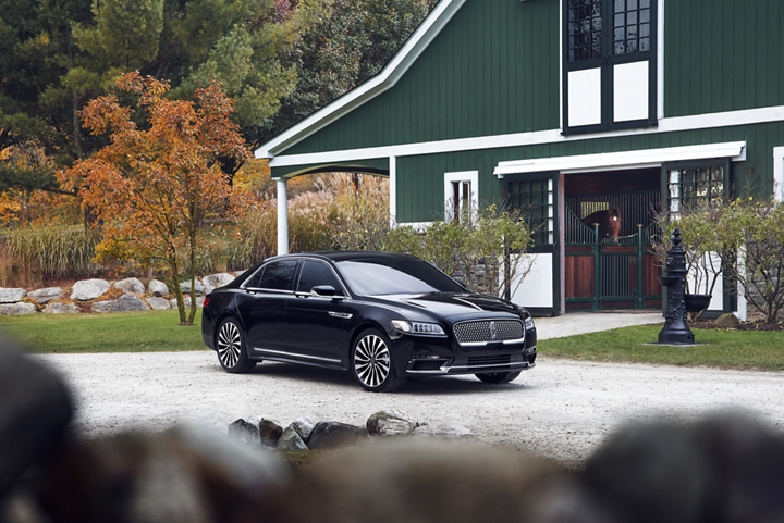 A 2020 Lincoln Black Label Continental is shown parked in front of a large and well kept horse stable