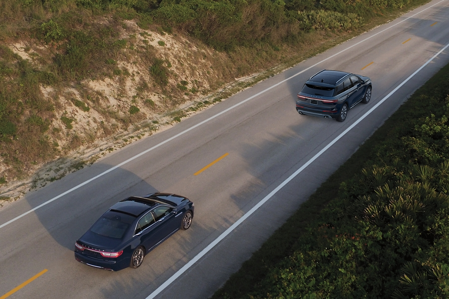 A 2020 Lincoln Continental is shown being driven on a road as it approaches another vehicle to demonstrate the capabilities of Adaptive Cruise Control