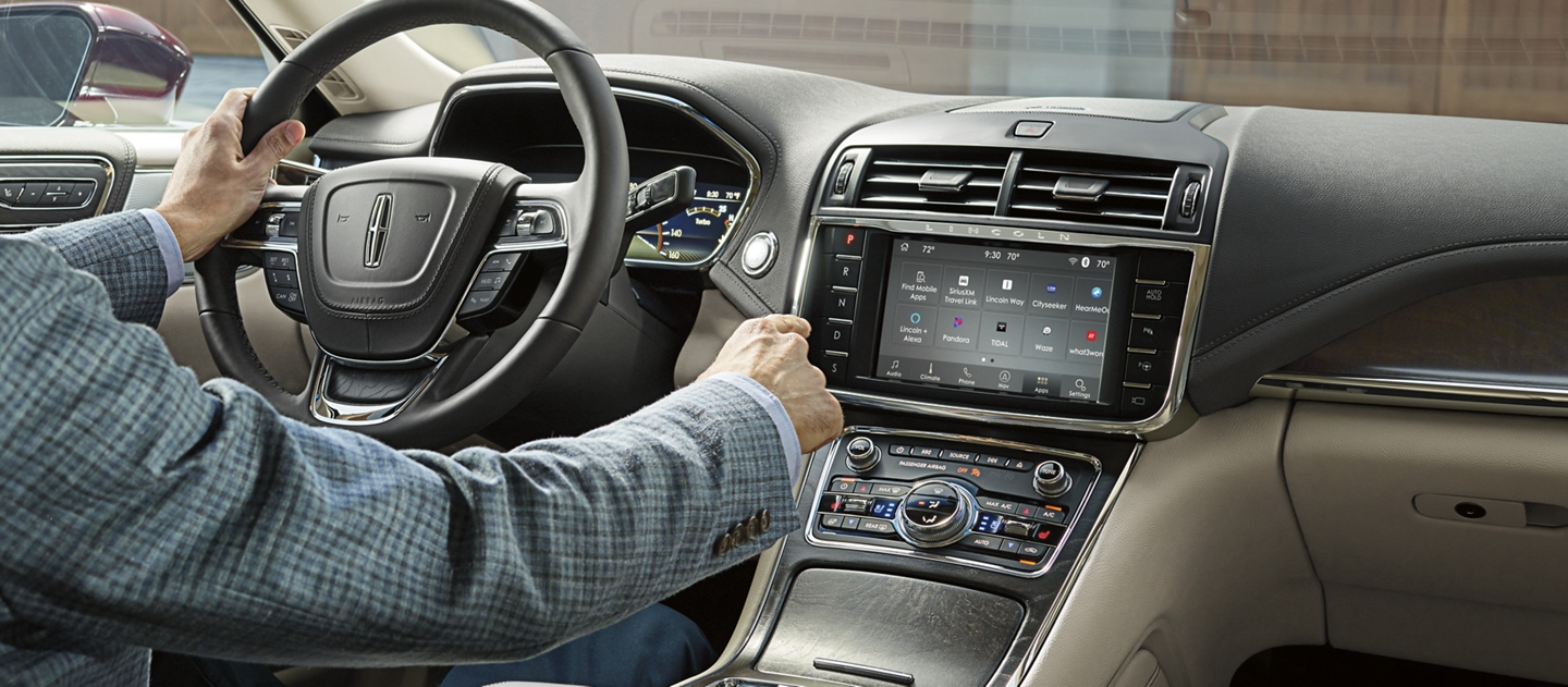 The driver of a 2020 Lincoln Continental is shown reaching for the center touch screen to demonstrate the WiFi capability