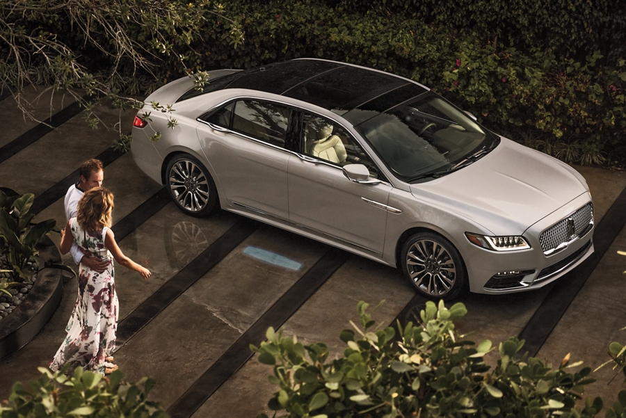 A splash of light is projected on the ground from a 2020 Lincoln Continental to help guide a couple as they approach