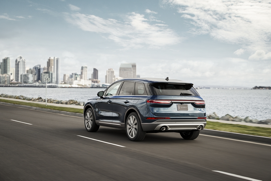 A 2020 Lincoln Corsair in flight blue is being driven on a city coast using Lincoln co pilot three sixty plus features