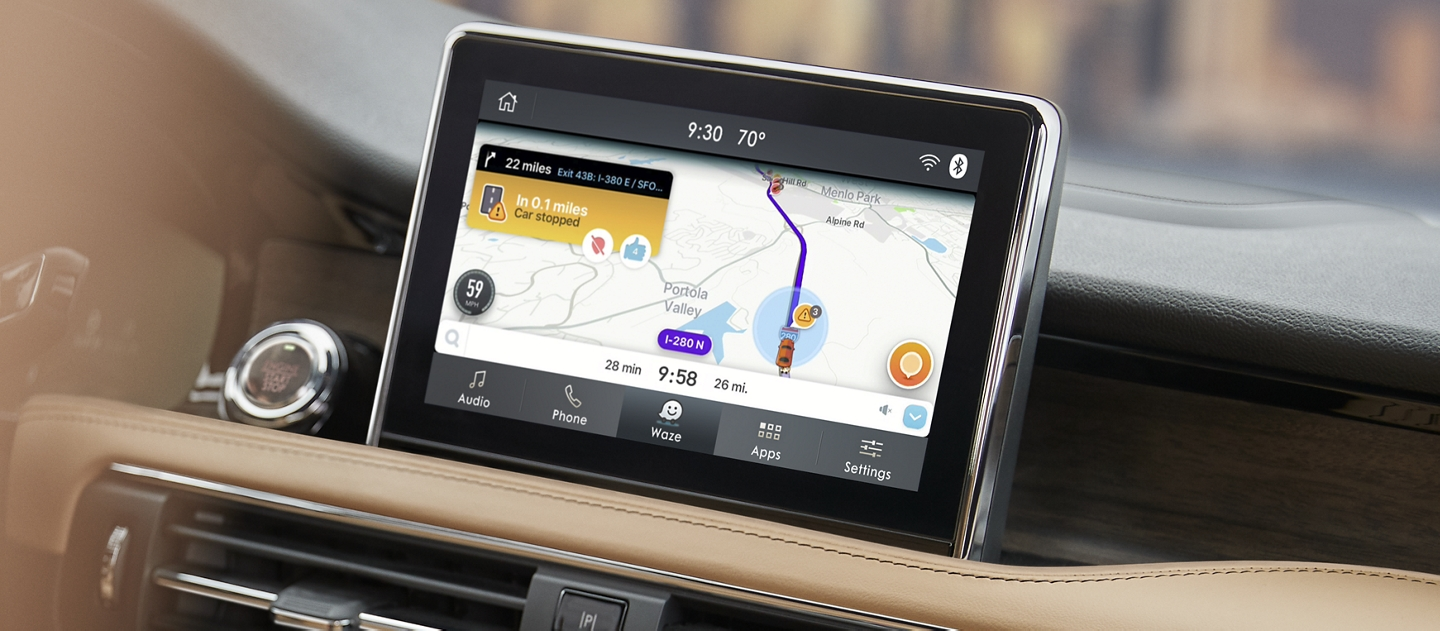 The center screen of a cashew interior is running the Waze navigation app on a broad digital display
