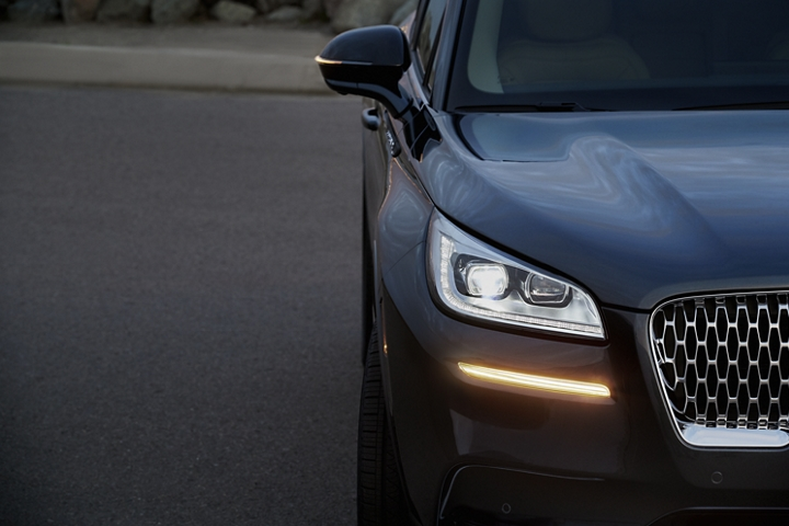 The turn signal on the front fascia is a bold sunset orange stroke of brilliance against a flight blue exterior