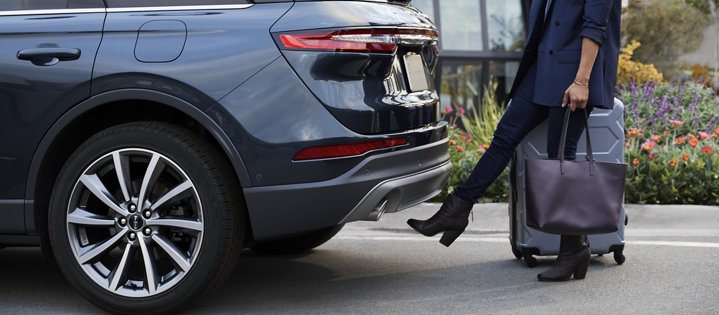 A woman with luggage and a bag easily opens the hands free power liftgate by kicking her foot under the bumper