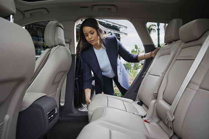 A woman slides the second row seat forward to create more cargo space