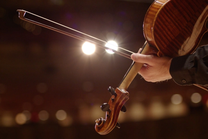 The bow of a D S O musicians violin slides across stage spotlights to illustrate the dramatic sound of the revel audio system