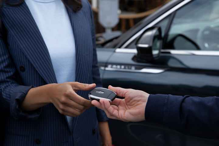 A Lincoln service representative hands a woman a key during pick up and delivery service in front of the drivers door of a 2020 Lincoln Corsair