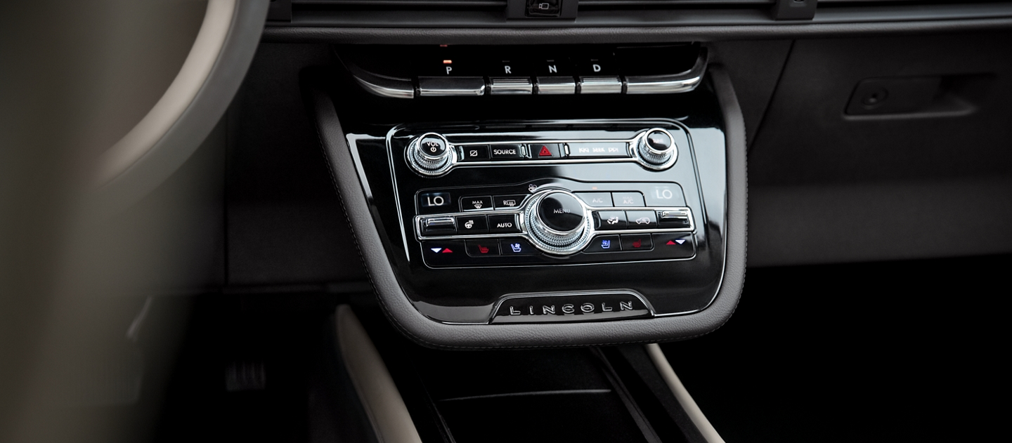 The floating center console shows off sleek controls featuring shiny black and bright chrome accents as well as open media storage space below