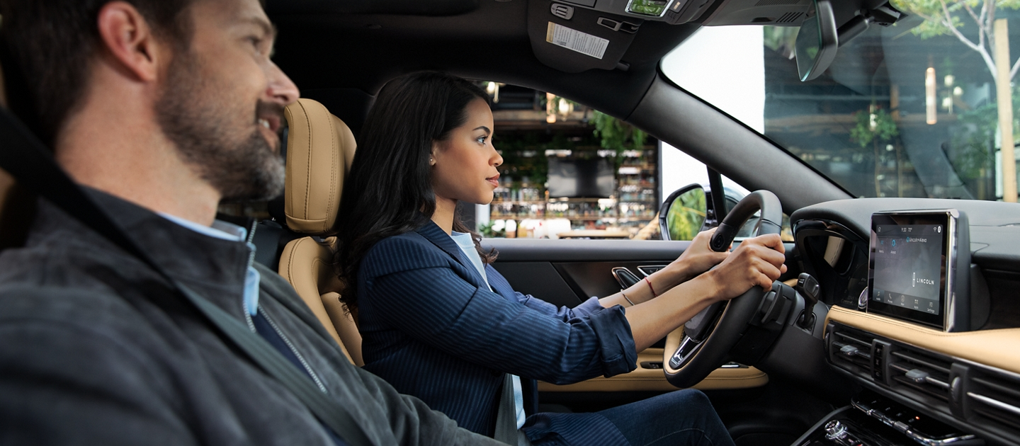 A woman in a blue pantsuit is driving a 2020 Lincoln Corsair through the city during the day as her male passenger speaks to Lincoln plus Alexa