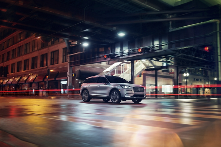 A 2020 Lincoln Corsair is being driven through a downtown intersection below an overpass at night with city lights bouncing off the road