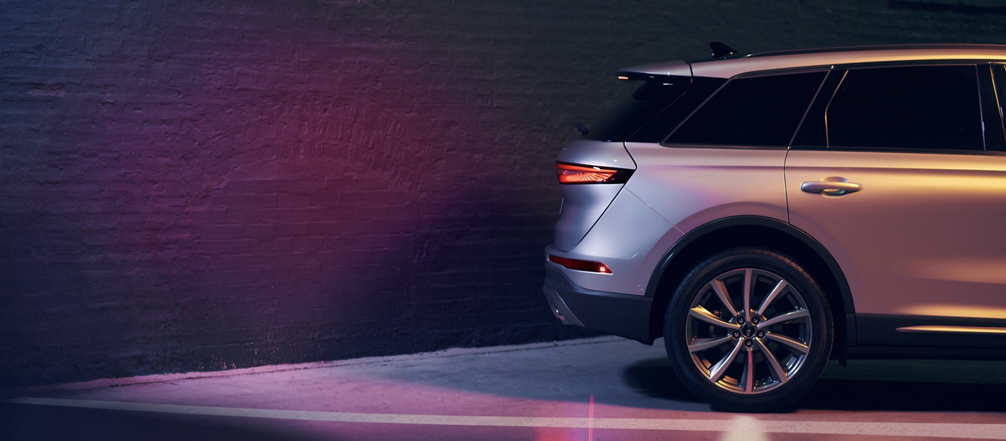 A 2020 Lincoln Corsair parked next to a building with illuminated brake lights demonstrates the reverse brake assist feature
