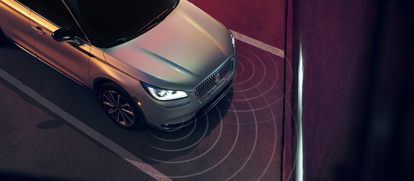 A 2020 Lincoln Corsair is being guided into a diagonal parking space as the headlamps illuminate the wall in front of the vehicle