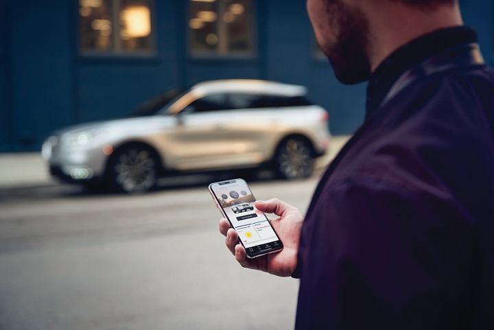 A man is holding his phone looking at the Lincoln Way App and we see his 2020 Lincoln Corsair in the background against a blue brick wall