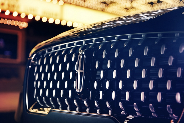 The reserve grille design shows floating chrome ovals that catch the glowing light of a theatre marquee and frame the distinctive Lincoln star