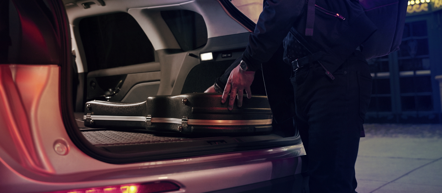 A musician slides his guitar case into the cargo area of a 2020 Lincoln Corsair with the rear seats folded flat to provide ample cargo space