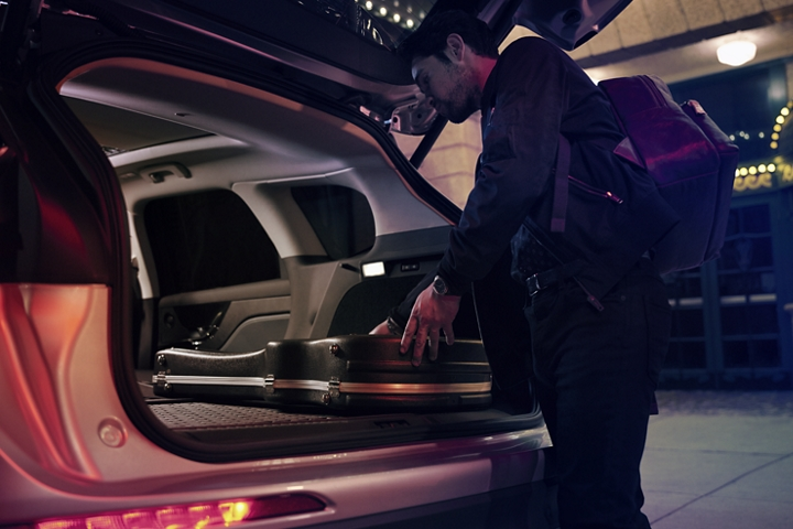 A musician slides his guitar case into the cargo space of a 2020 Lincoln Corsair with the rear seats folded flat to provide ample cargo space