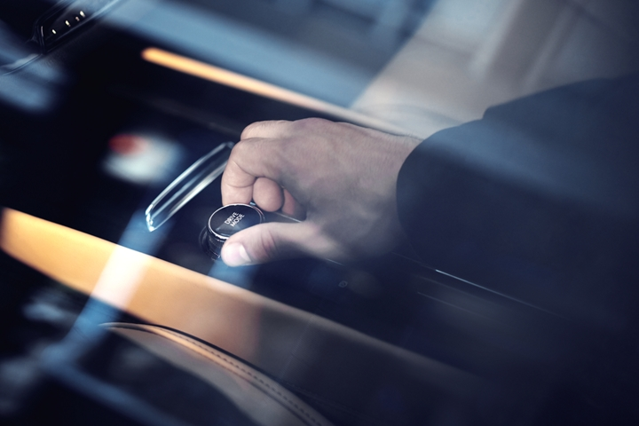 Through an exterior window reflecting surrounding skyscrapers we see a drivers hand turning the Lincoln drive modes knob near the center console