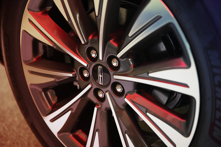 A detail shot of a wheel shows off blade like chrome spokes that catch and reflect different angles of daylight with a red glow
